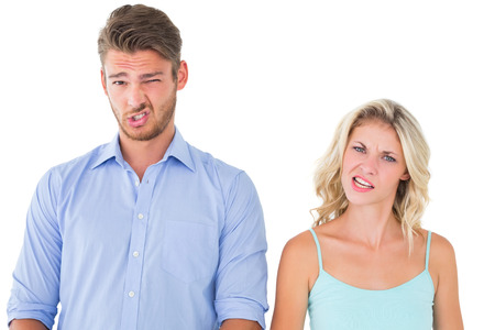 confused woman: Young couple making silly faces on white background