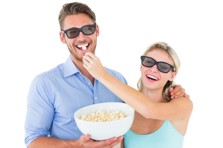 Happy young couple wearing 3d glasses eating popcorn on white background photo