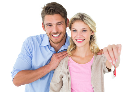 Attractive young couple showing new house key on white background photo
