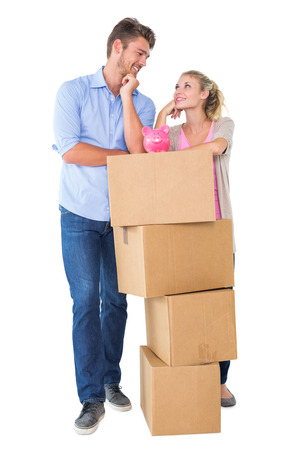 Attractive young couple leaning on boxes with piggy bank on white background photo