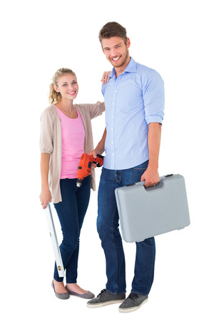Young couple holding diy tools on white background photo