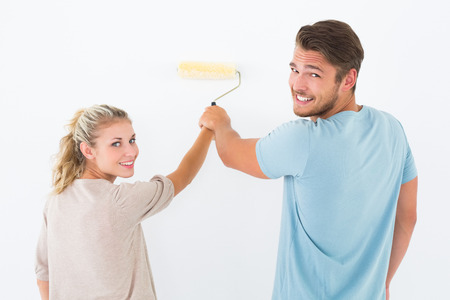 Young couple painting with roller on white background photo