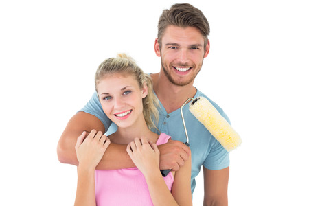 Young couple hugging and holding paint roller on white background photo