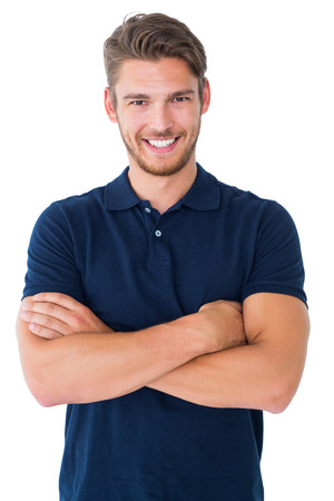 Knappe jonge man glimlachend met de armen gekruist op een witte achtergrond