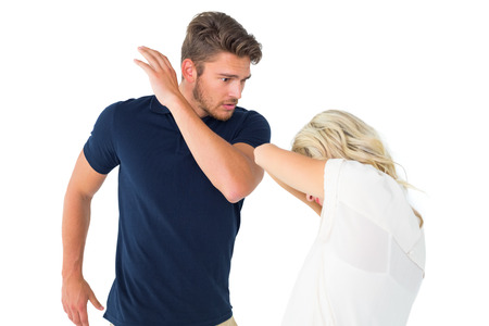 Angry man about to hit his girlfriend on white background photo