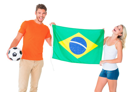 Excited football fan couple holding brazil flag on white background photo