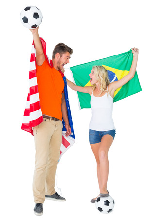 Excited football fan couple holding usa and brazils flag on white background photo
