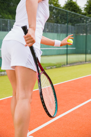 Tennis player getting ready to serve on a sunny day photo