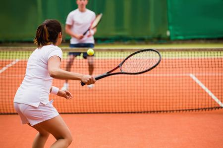 Tennissers spelen van een wedstrijd op de baan op een zonnige dag