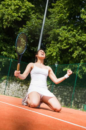 Pretty tennis player celebrating a win on a sunny day photo