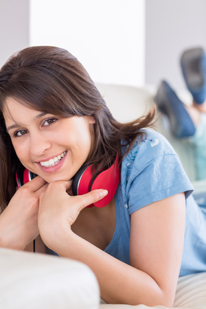 Pretty brunette wearing earphones around neck on the couch at home in the living room photo