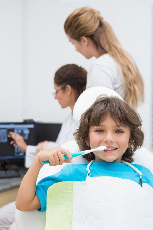 Little boy smiling at camera with mother and dentist in background at the dental clinic photo
