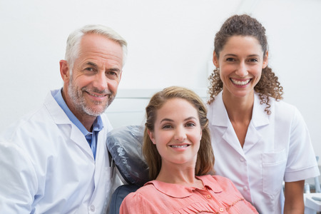 Dentist his assistant and patient all smiling at camera at the dental clinic photo