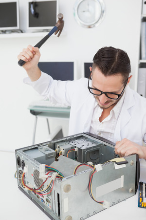 Angry computer engineer holding hammer over console in his office photo