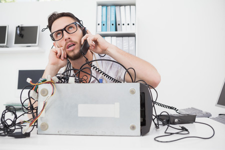 Annoyed computer engineer making a call in his office
