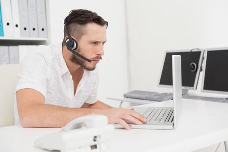 call center agent: Agente della call center in una chiamata alla sua scrivania nel suo ufficio Archivio Fotografico