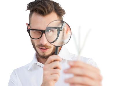白い背景の上に虫眼鏡を通して見るオタクの実業家