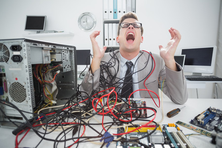 Stressed computer engineer working on broken cables in his office photo