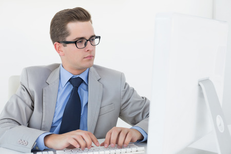 businessman working at his computer: Nerdy businessman working on computer in his office