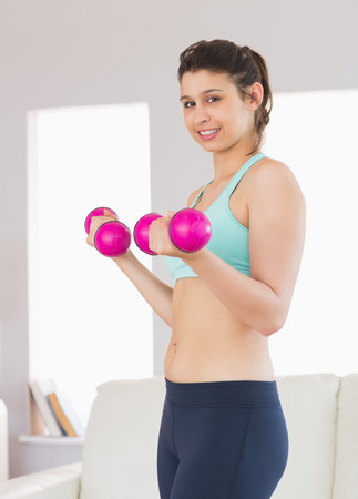 Fit brunette holding pink dumbbells at home in the living room photo