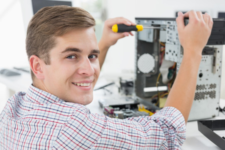 it technology: Young technician working on broken computer in his office Stock Photo