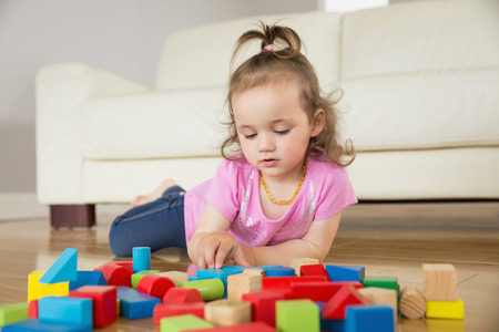 Cute little girl playing with building blocks on floor at home photo