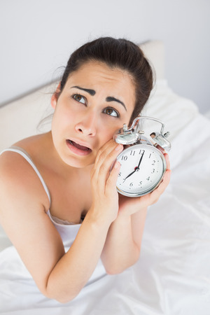 fed up: Beautiful annoyed young woman holding an alarm clock while sitting in bed at home