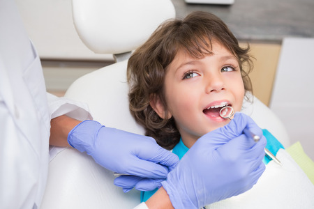 Pediatric dentist examining a little boys teeth in the dentists chair at the dental clinic photo