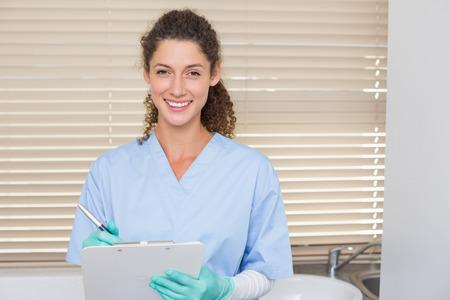 Dentist in blue scrubs writing on clipboard at the dental clinic Standard-Bild