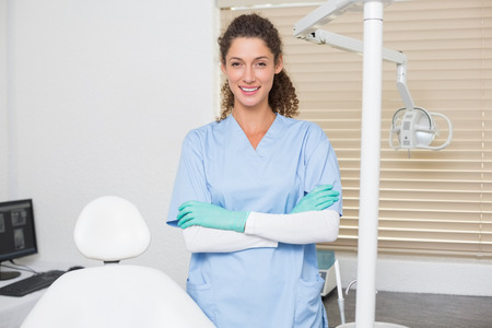 Dentist in blue scrubs smiling at camera beside chair at the dental clinic photo