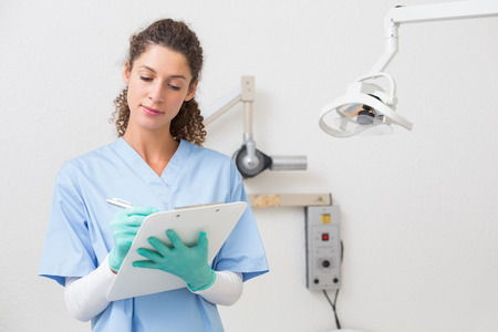 Dentist in blue scrubs writing on clipboard at the dental clinic photo