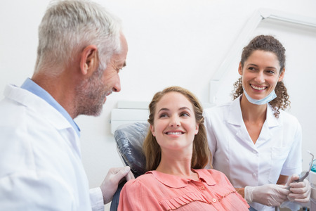 Dentist talking with patient while nurse prepares the tools at the dental clinic Banco de Imagens