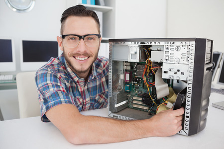 pc repair: Computer engineer working on broken console smiling at camera in his office Stock Photo