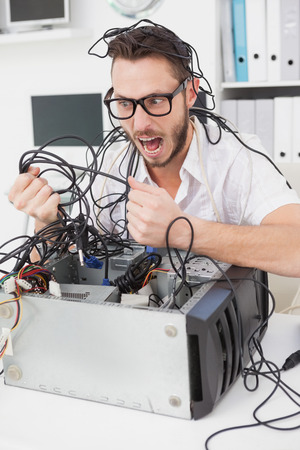 Angry computer engineer pulling wires in his office photo