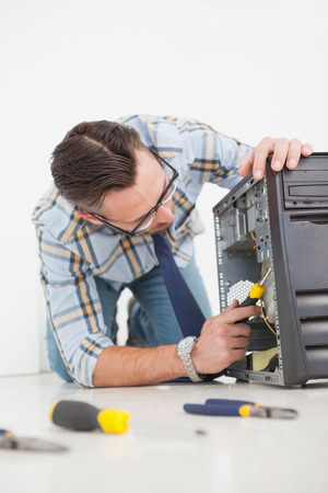 Computer engineer working on broken console with screwdriver in his office photo