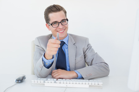 businessman working at his computer: Nerdy businessman working on computer pointing at camera in his office