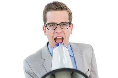 Nerdy businessman shouting through megaphone on white background photo