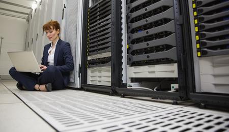Technician sitting on floor beside server tower using laptop in large data center photo
