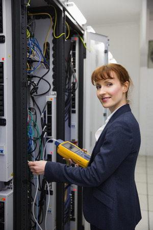 Happy technician using digital cable analyzer on server  in large data center photo