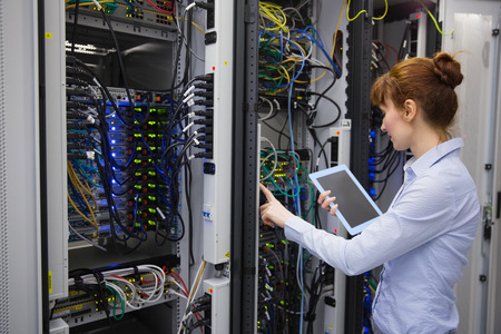 Technician using tablet pc while analysing server in large data center photo