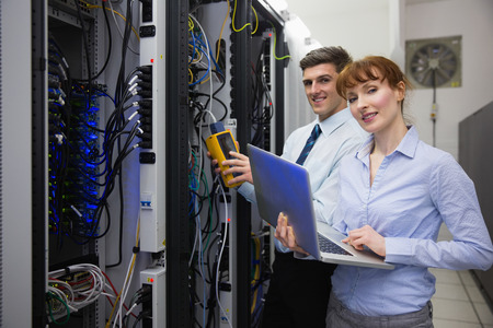 programmer computer: Team of technicians using digital cable analyser on servers in large data center