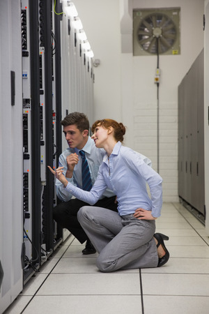 Team of technicians kneeling and looking at servers in large data center photo
