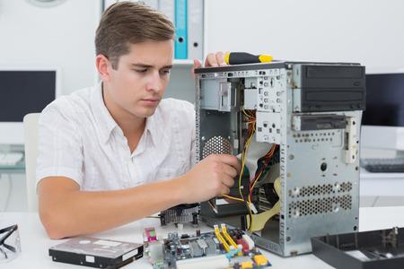 Jonge technicus werkt aan kapotte computer in zijn kantoor Stockfoto