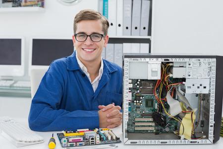 it technician: Smiling technician working on broken computer in his office