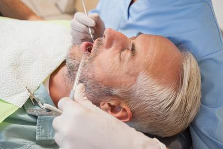 Dentist examining a patients teeth in the dentists chair at the dental clinic Stock Photo