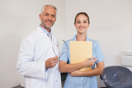Dentist and assistant smiling at camera at the dental clinic photo