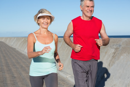 healthy path: Active senior couple out for a jog on a sunny day