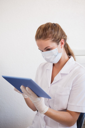 Dental assistant working on tablet pc at the dental clinic photo
