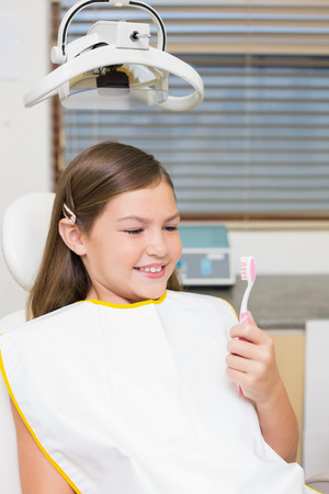 Little girl holding toothbrush in dentists chair at the dental clinic photo