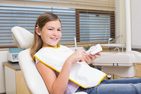 Little girl sitting in dentists chair looking at model teeth at the dental clinic photo